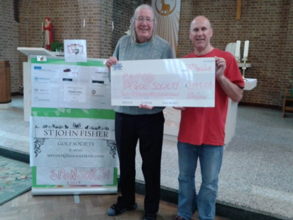 Fr Tom and Harry Cissell hold a cheque for £2114.09 for CAFOD