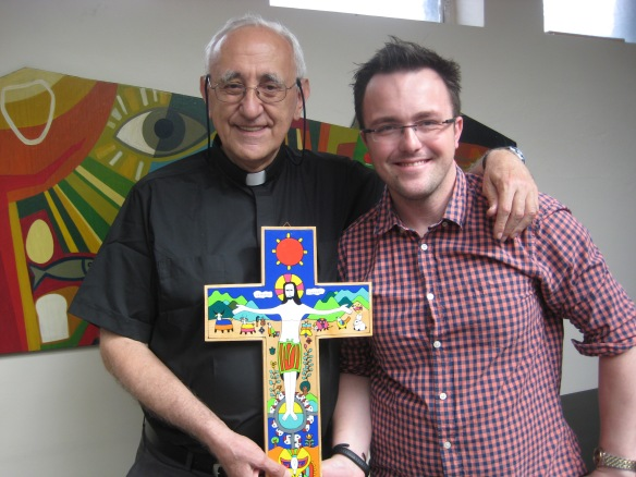 Father Carlo Bonelli (left) visits Jon Stricklin-Coutinho (right) and volunteers at the CAFOD Westminster office.