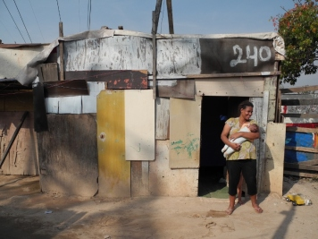 Anna Paula and her 3 month old daughter Alexandra Victoria in front of their home in Electropaulo Favela