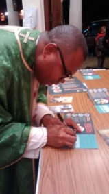 Fr Chinedu signing a Power to Be campaign card